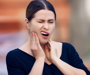 Woman with lost filling holding jaw in pain