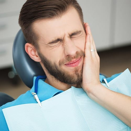Man holding cheek during emergency dentistry treatment