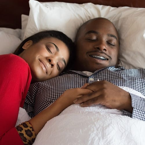 Man with sleep apnea treatment sleeping soundly with his wife