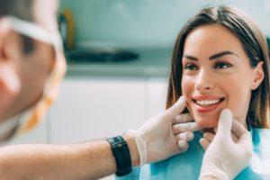 cosmetic dentist examining patient's teeth