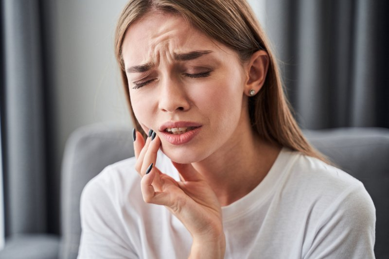 a young woman holds her mouth in pain because of a toothache in Fort Myers