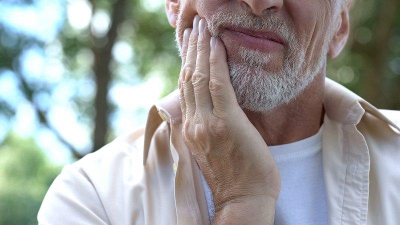 Closeup of man experiencing sensitivity in dental implant
